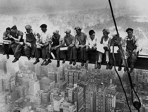 A picture of early 20th century immigrants working on a construction site overlooking New York City